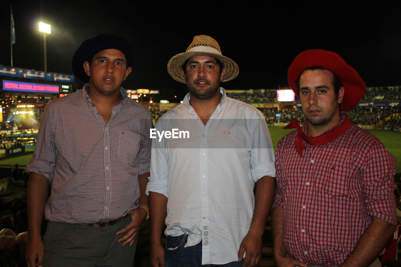 looking at camera, portrait, waist up, night, front view, young adult, standing, young men, real people, togetherness, illuminated, outdoors