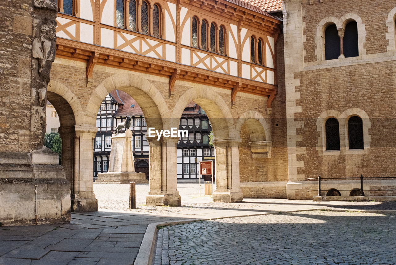 architecture, arch, built structure, history, the past, building, building exterior, city, day, window, old, no people, entrance, sunlight, travel destinations, architectural column, outdoors, street, shadow, door, courtyard, gothic style, arched, ancient civilization