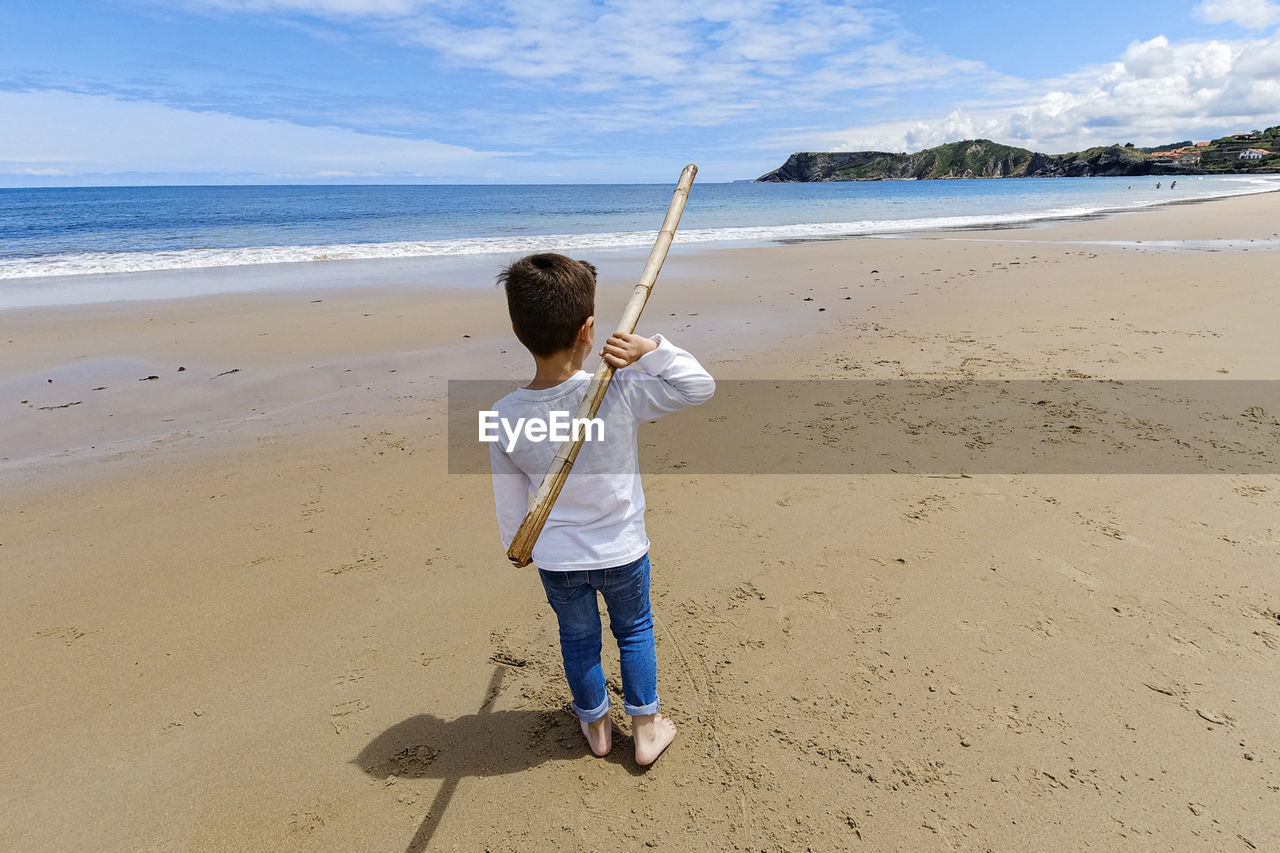 Rear view of boy holding stick while standing at beach
