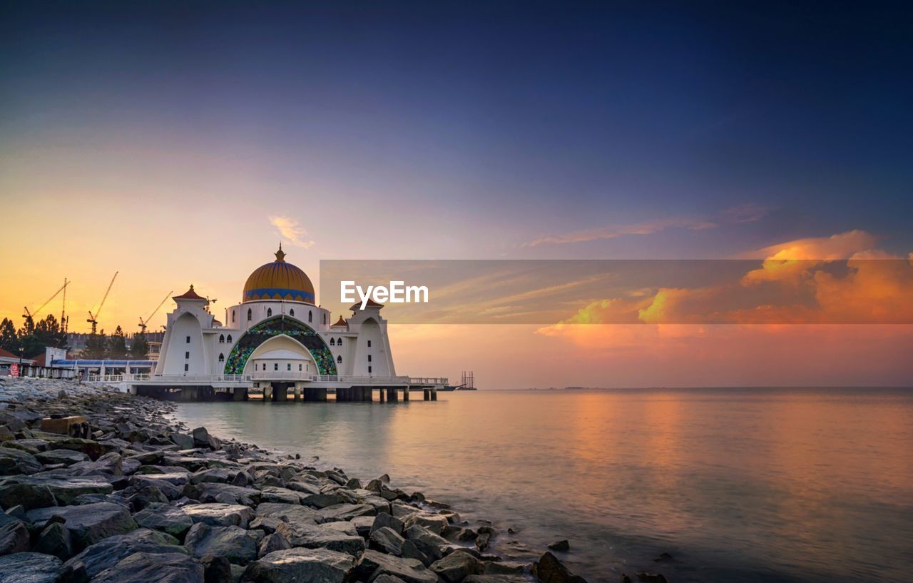 sky, water, sunset, building exterior, built structure, architecture, religion, belief, place of worship, spirituality, dome, building, orange color, nature, travel destinations, sea, scenics - nature, no people