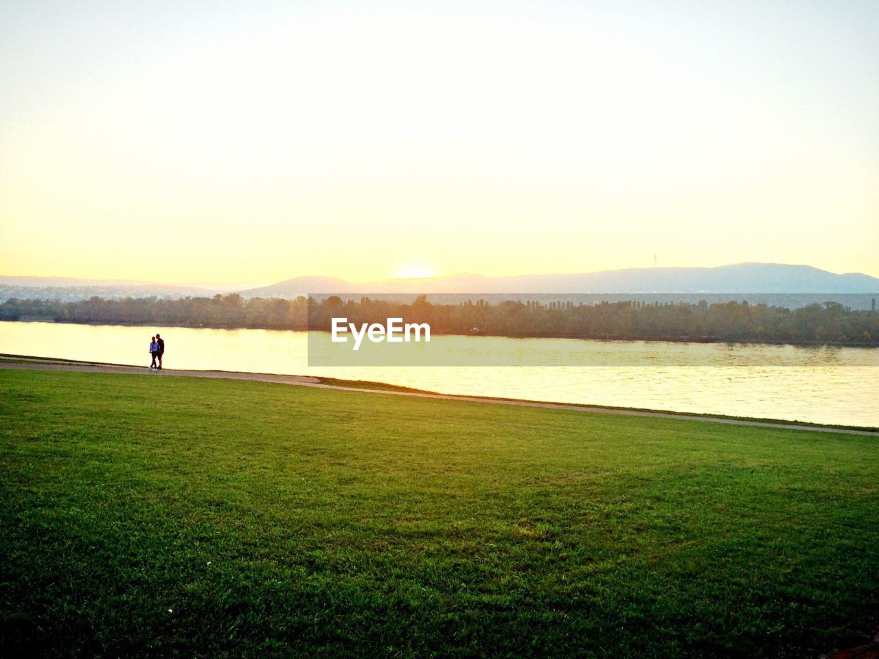 grass, sunset, nature, lake, scenics, water, beauty in nature, silhouette, tranquil scene, golf course, leisure activity, golf, outdoors, one person, lifestyles, landscape, people, adult, standing, full length, sky, mountain, real people, adults only, golfer, clear sky, green - golf course, only women, golf club, one woman only, day