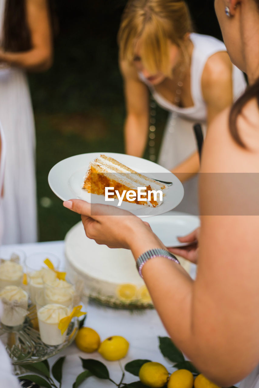 Midsection of woman holding cake in plate