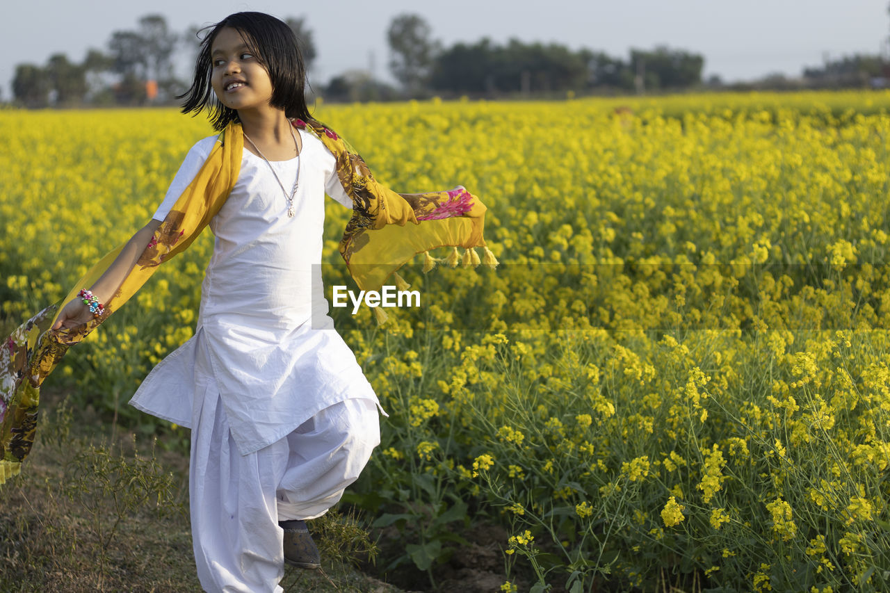 BEAUTIFUL YOUNG WOMAN STANDING ON FIELD WITH YELLOW FLOWERS IN BACKGROUND