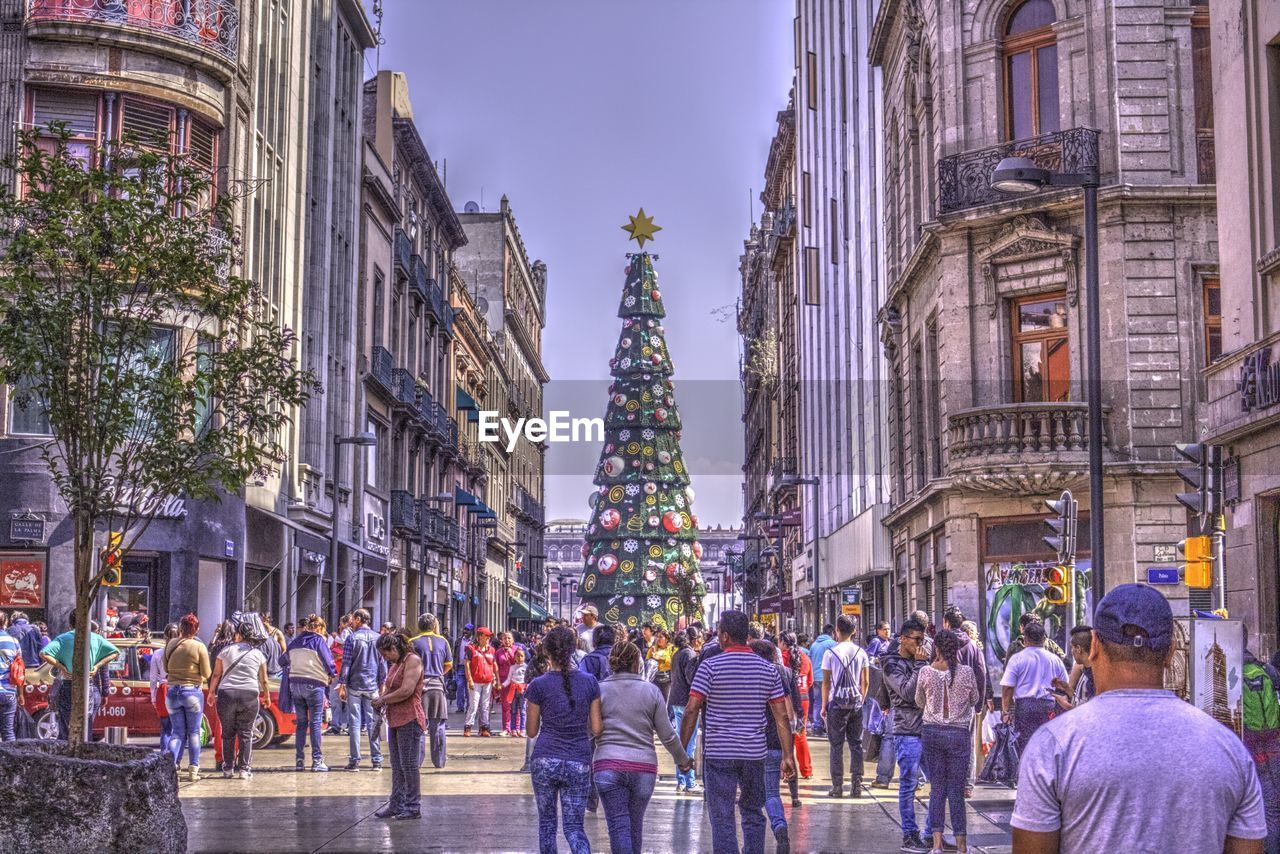 architecture, large group of people, built structure, building exterior, real people, walking, men, women, city, lifestyles, day, tree, outdoors, crowd, sky, adult, people