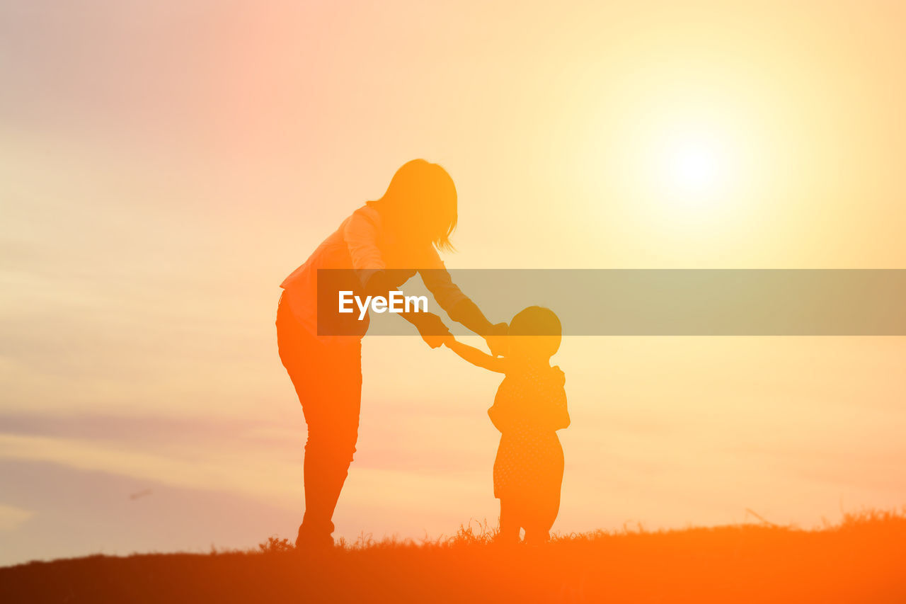 Silhouette mother and daughter standing on field against orange sky