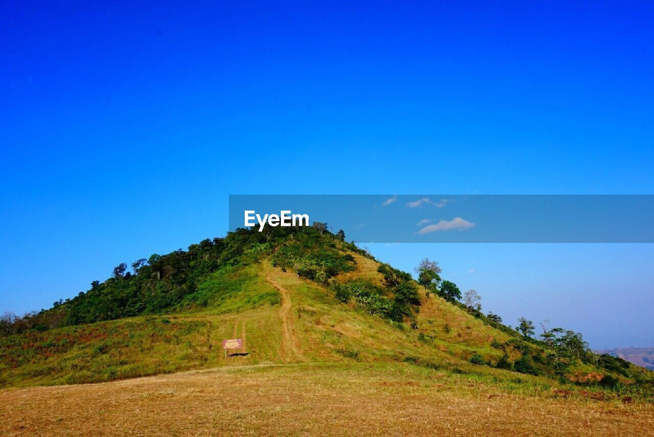 Scenic view of hill against blue sky