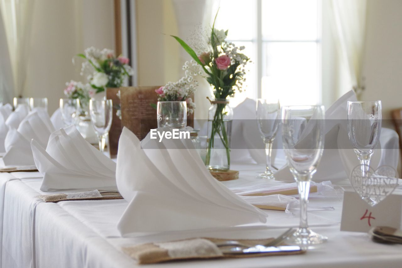 table, furniture, glass, place setting, napkin, setting, flowering plant, dining table, plate, indoors, wineglass, flower, plant, celebration, drinking glass, vase, household equipment, decoration, arrangement, nature, no people, flower arrangement, table knife