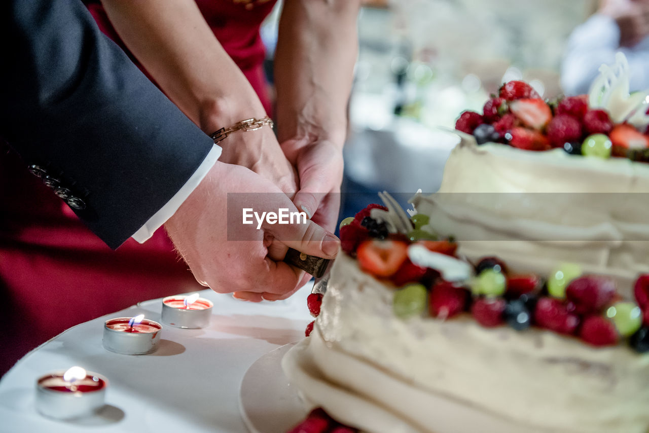 Cropped Hands Of Newlywed Couple Cutting Cake In Wedding Ceremony