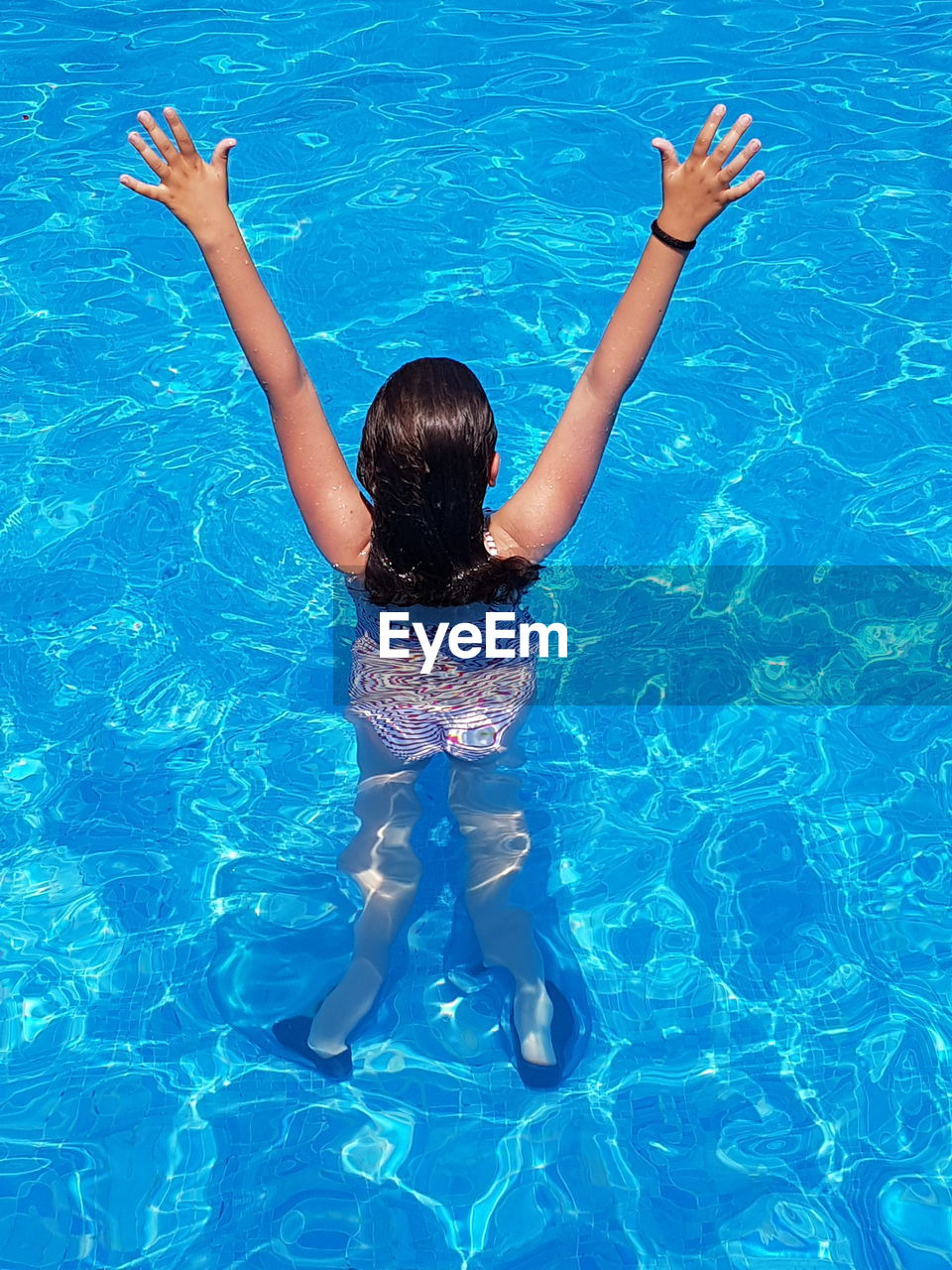 High angle rear view of girl standing with arms raised in swimming pool