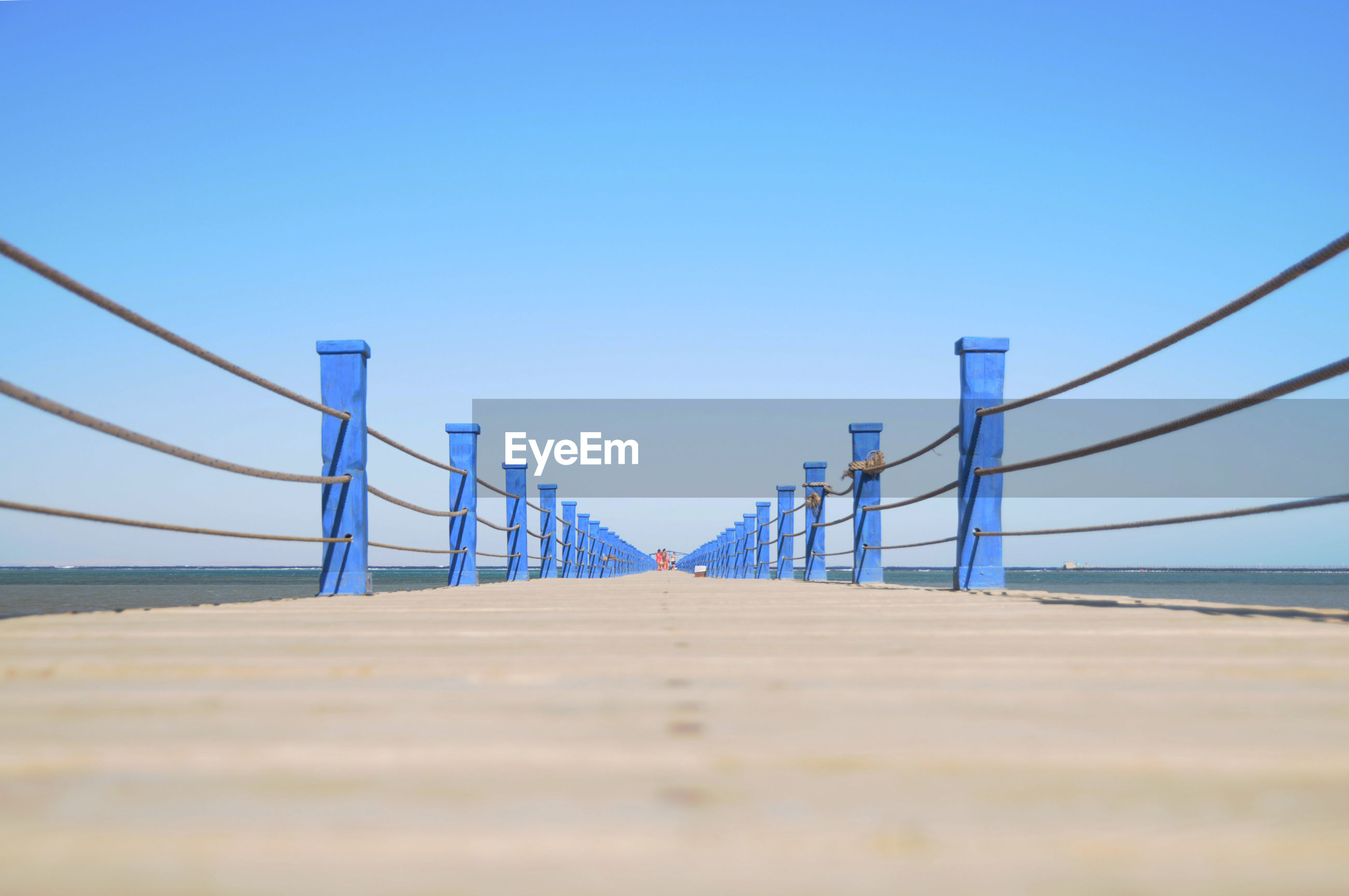 Surface level of bridge against clear blue sky