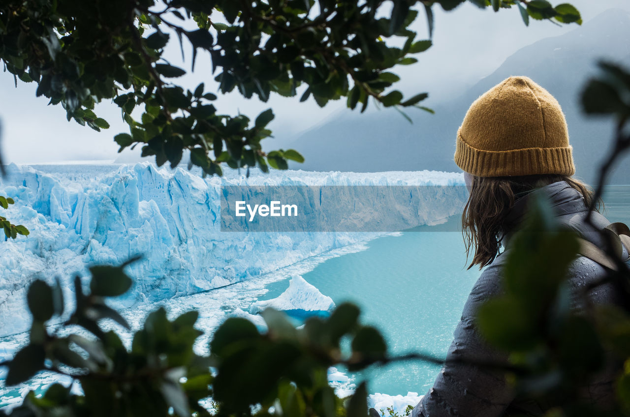Rear view of woman looking at glacier during winter