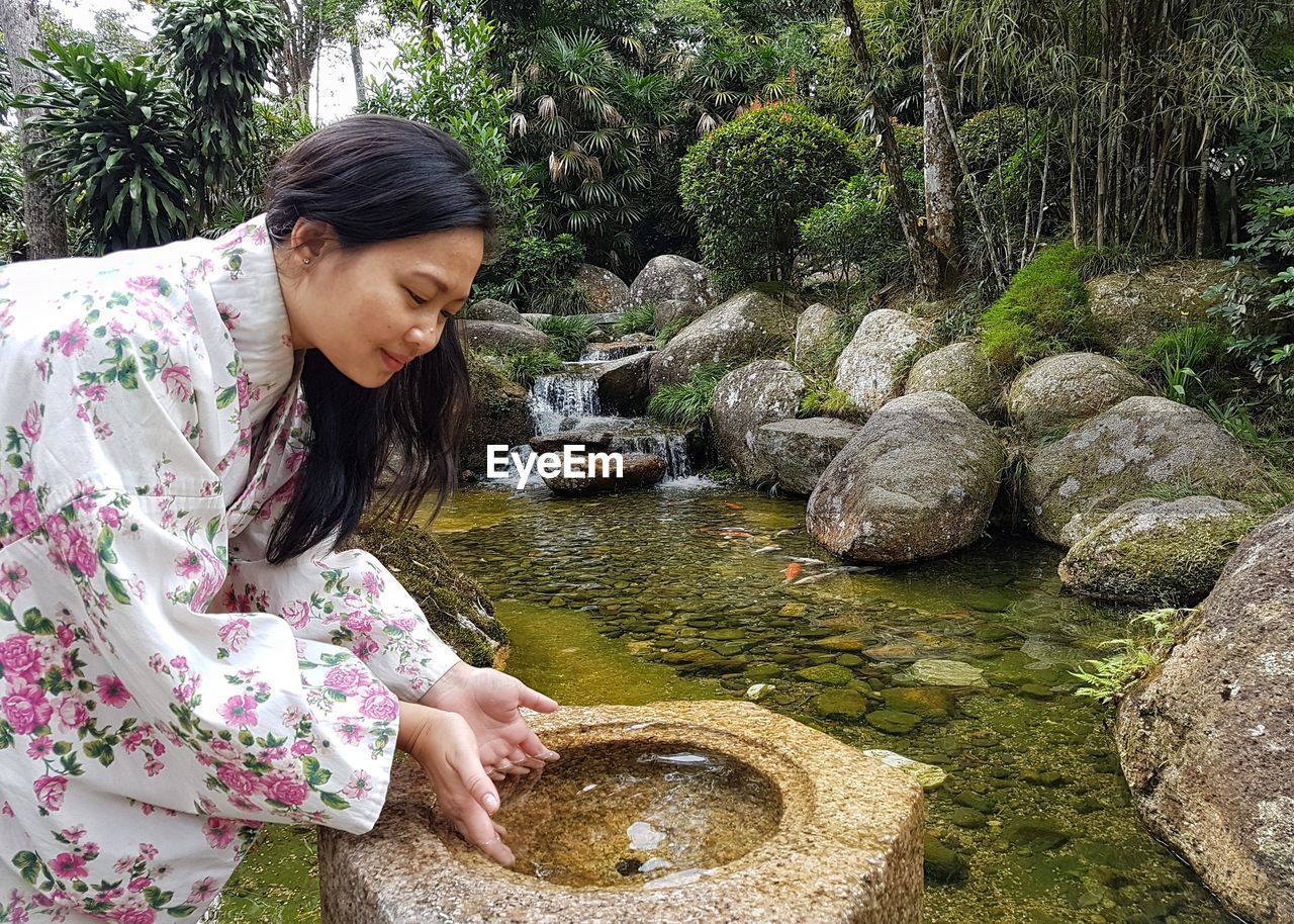 Smiling woman wearing kimono while putting hand in water at park