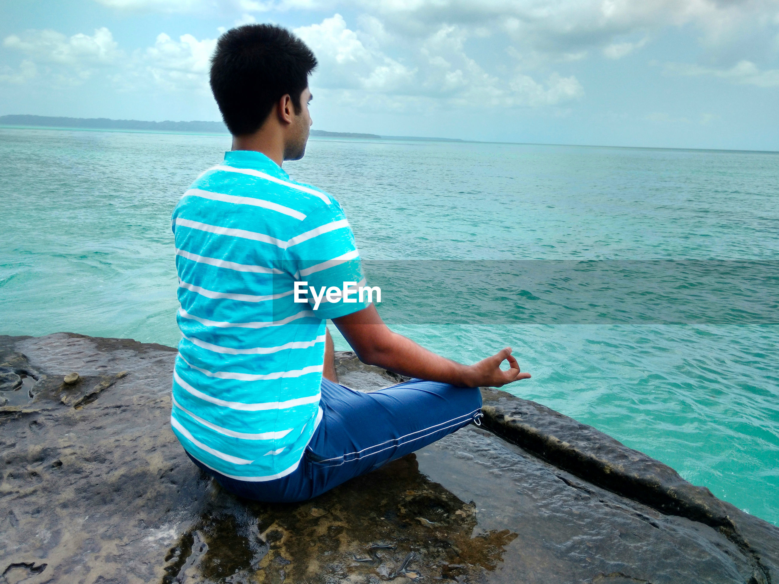 Rear view of man meditating on wet rock by sea against cloudy sky