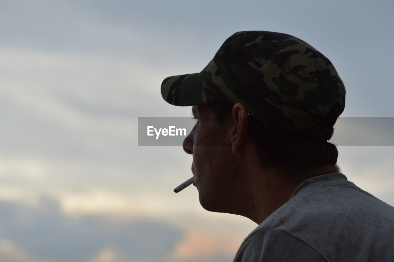 Man wearing cap smoking against sky