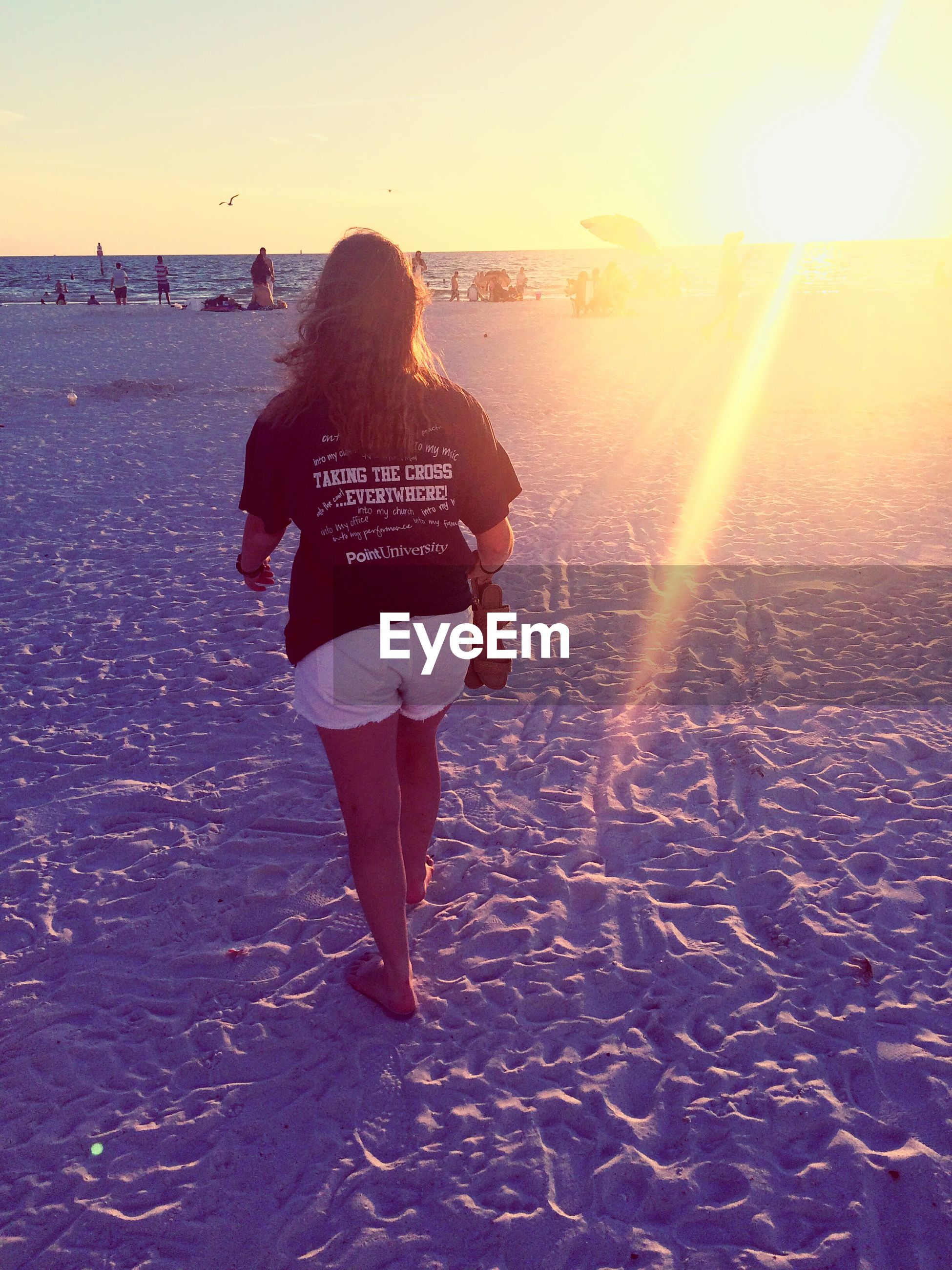lifestyles, beach, full length, leisure activity, sunlight, sand, sunset, rear view, shore, sun, sea, walking, casual clothing, standing, water, person, sky, vacations