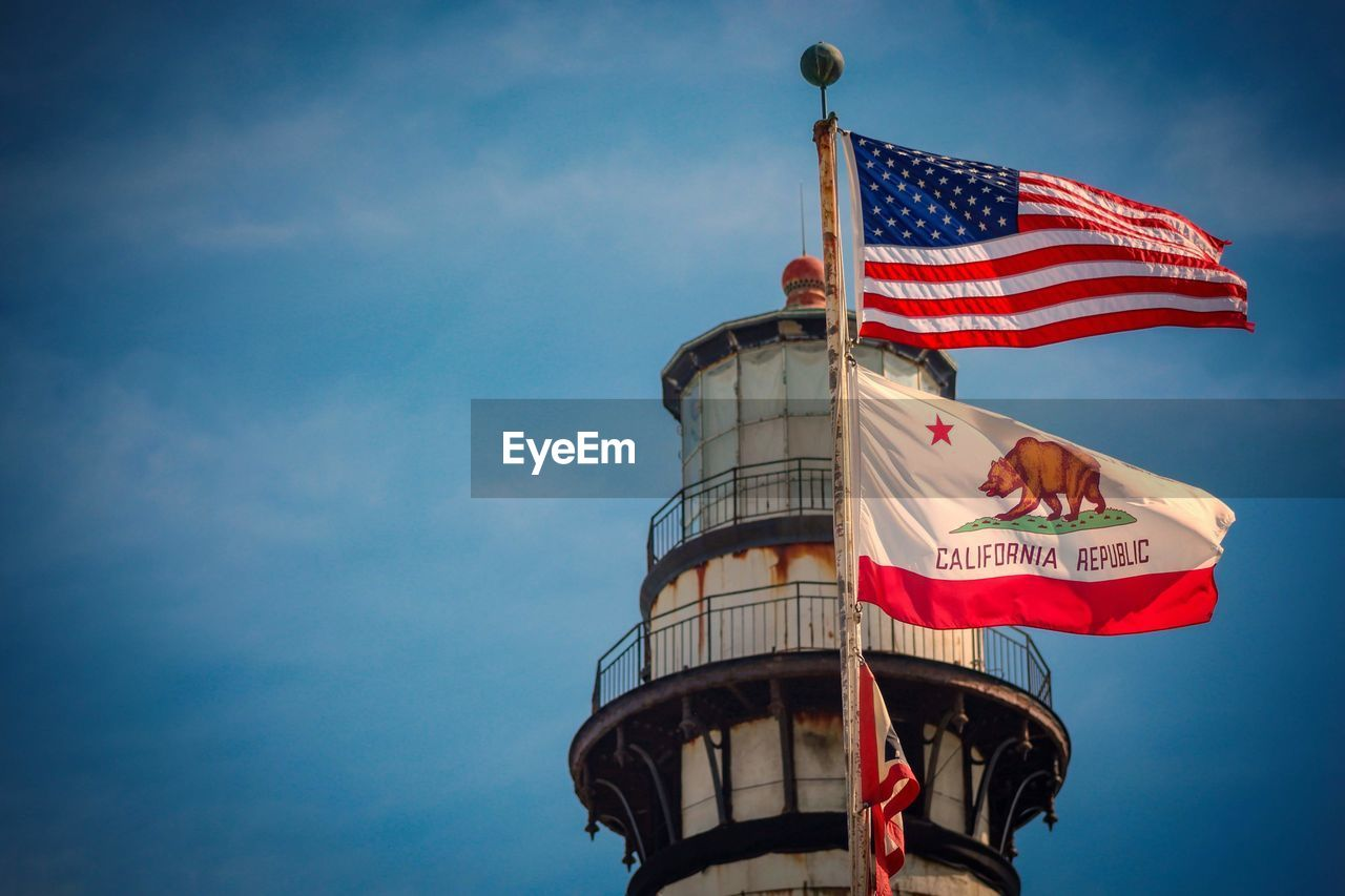 sky, flag, low angle view, patriotism, striped, nature, blue, architecture, day, cloud - sky, built structure, building exterior, wind, pride, outdoors, independence, freedom, waving, national icon, no people