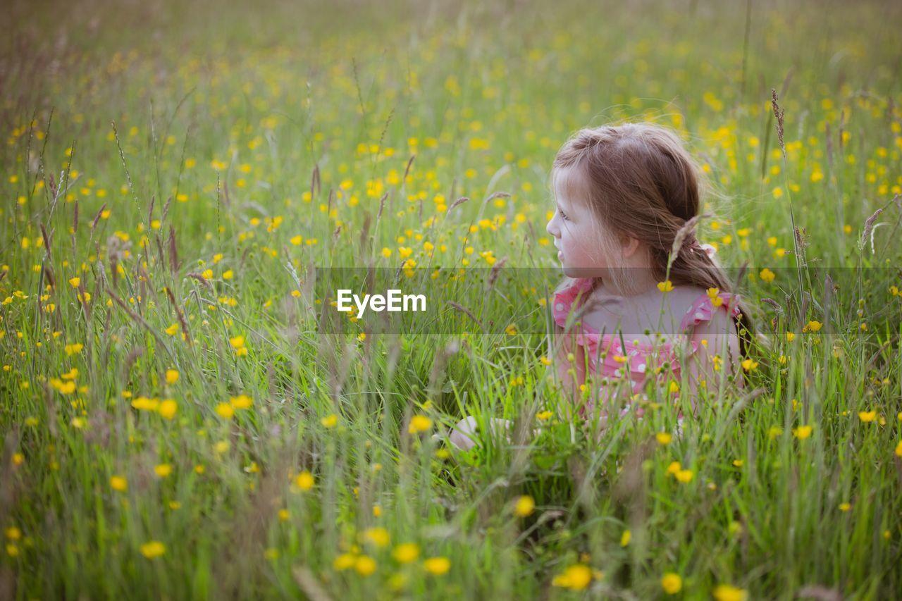 Girl sitting on blooming flowers