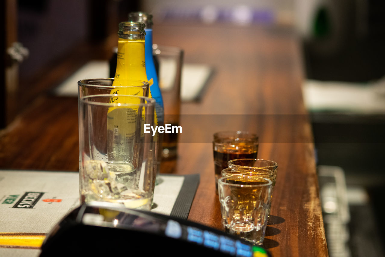 table, food and drink, drink, glass, refreshment, household equipment, drinking glass, alcohol, indoors, close-up, still life, business, no people, restaurant, focus on foreground, transparent, freshness, food, selective focus, container, tray