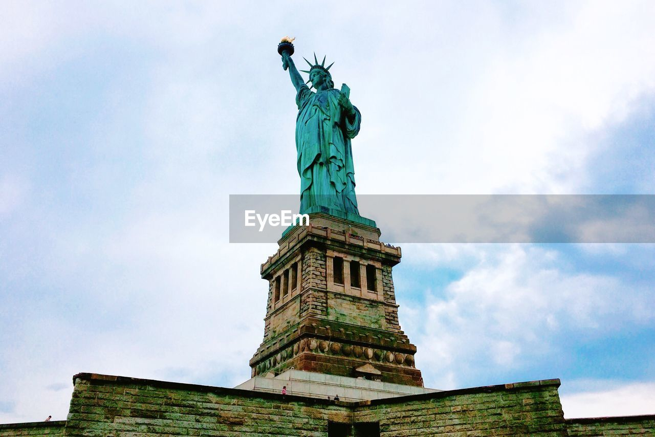sky, low angle view, sculpture, statue, cloud - sky, representation, human representation, art and craft, architecture, female likeness, travel destinations, nature, day, no people, tourism, travel, built structure, flame, the past, freedom, turquoise colored