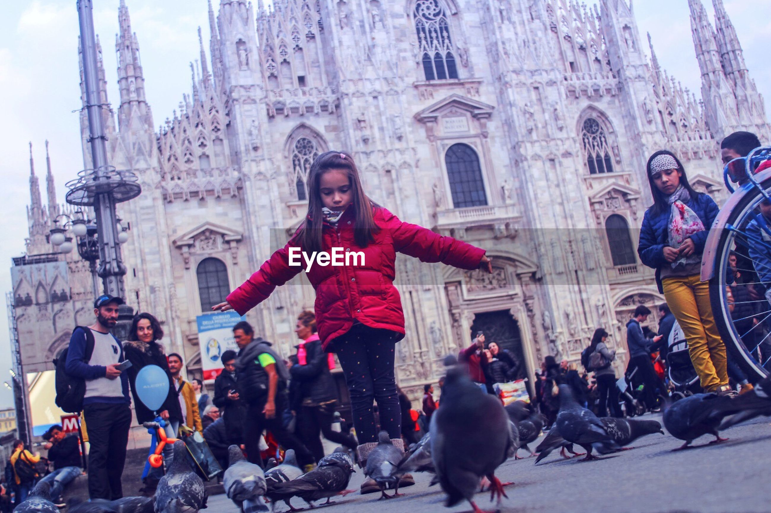 People and pigeons outside duomo di milano