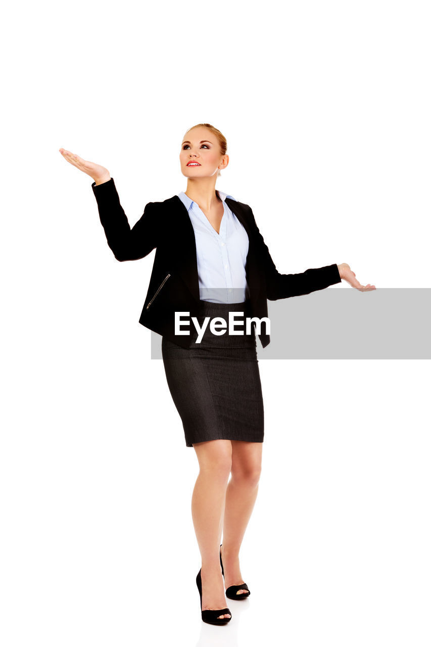 Businesswoman gesturing while standing against white background