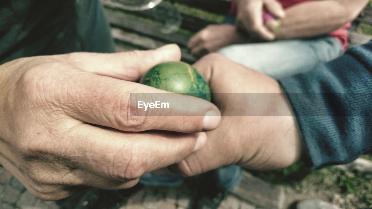 Close-Up Of Hands Holding Easter Egg