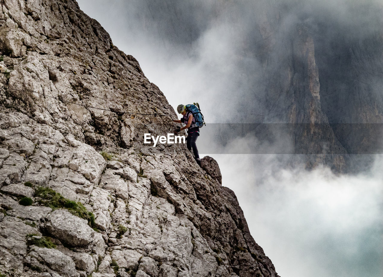 Low Angle View Of Woman Climbing On Mountain Against Sky