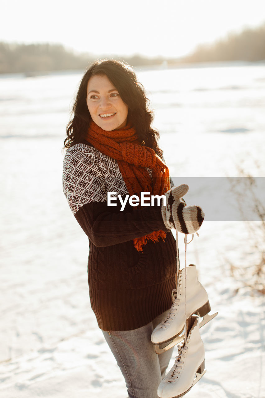 Smiling Woman Standing On Snow Covered Field