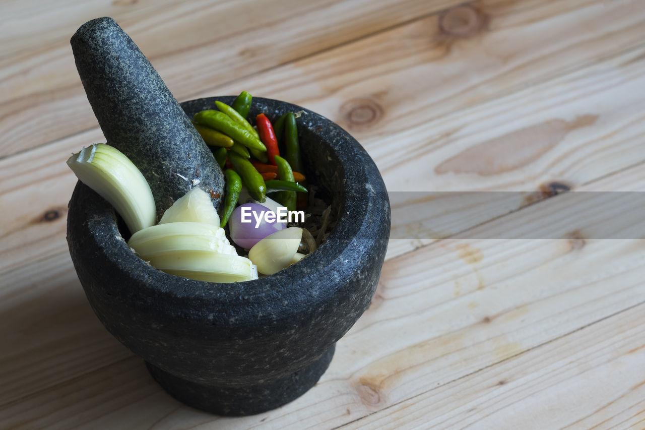 food, food and drink, wood - material, table, still life, close-up, freshness, no people, vegetable, healthy eating, pepper, indoors, wellbeing, high angle view, focus on foreground, spice, bowl, choice, variation, olive
