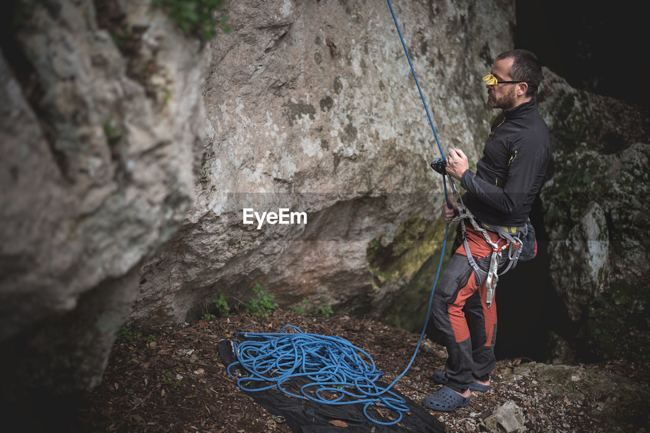 rock, rock - object, one person, real people, solid, leisure activity, activity, rock formation, lifestyles, adventure, holding, climbing, nature, sport, day, rock climbing, full length, rope, young men, outdoors, safety harness