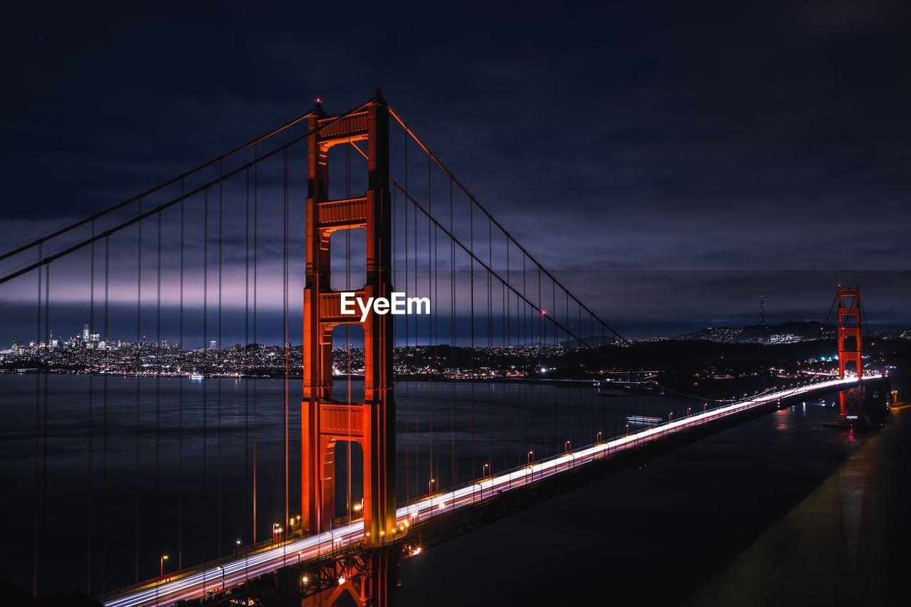 Golden gate bridge over bay against sky at night