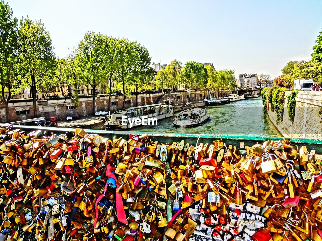 padlock, love lock, abundance, railing, love, day, bridge - man made structure, lock, tree, architecture, outdoors, hope, water, clear sky, built structure, river, large group of objects, hanging, no people, hope - concept, sky, building exterior