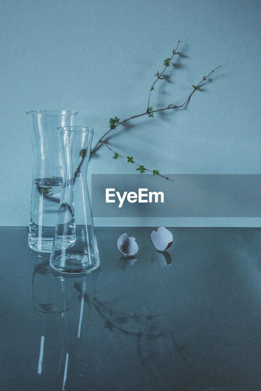 CLOSE-UP OF GLASS VASE ON TABLE AGAINST BLUE WALL