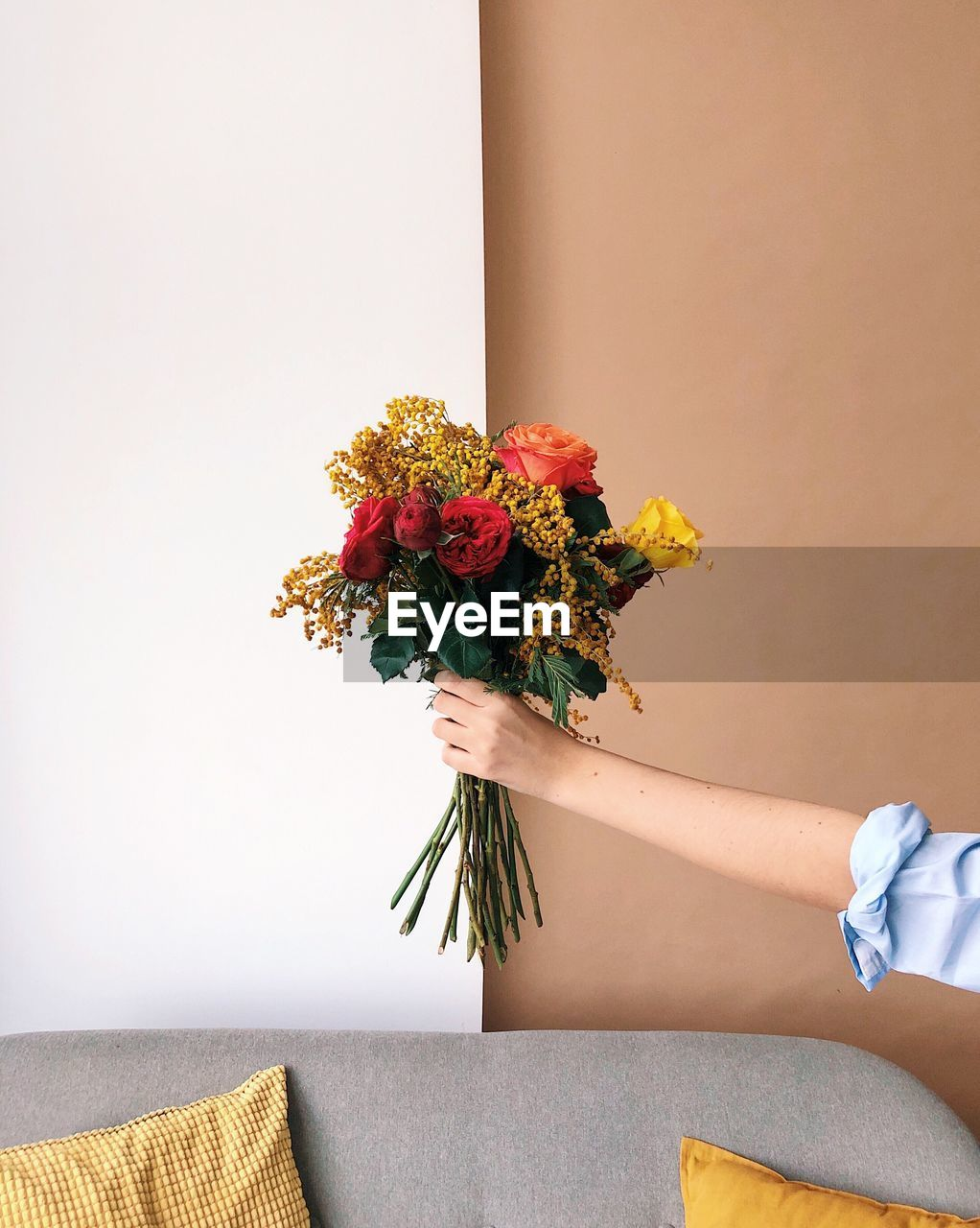 flowering plant, flower, plant, indoors, flower arrangement, wall - building feature, nature, vulnerability, bouquet, fragility, beauty in nature, women, real people, one person, freshness, human hand, vase, human body part, hand, holding, flower head, bunch of flowers