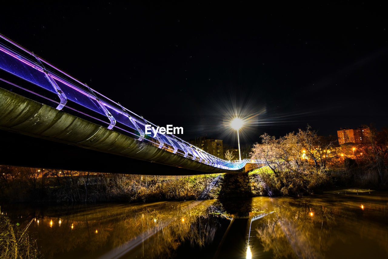 LIGHT TRAILS OVER RIVER AGAINST SKY AT NIGHT