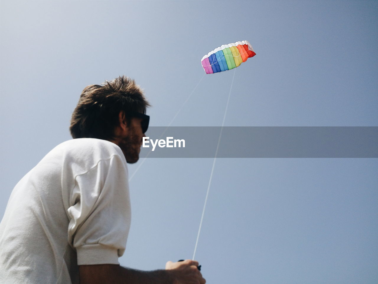 Low angle view of man flying kite against clear sky