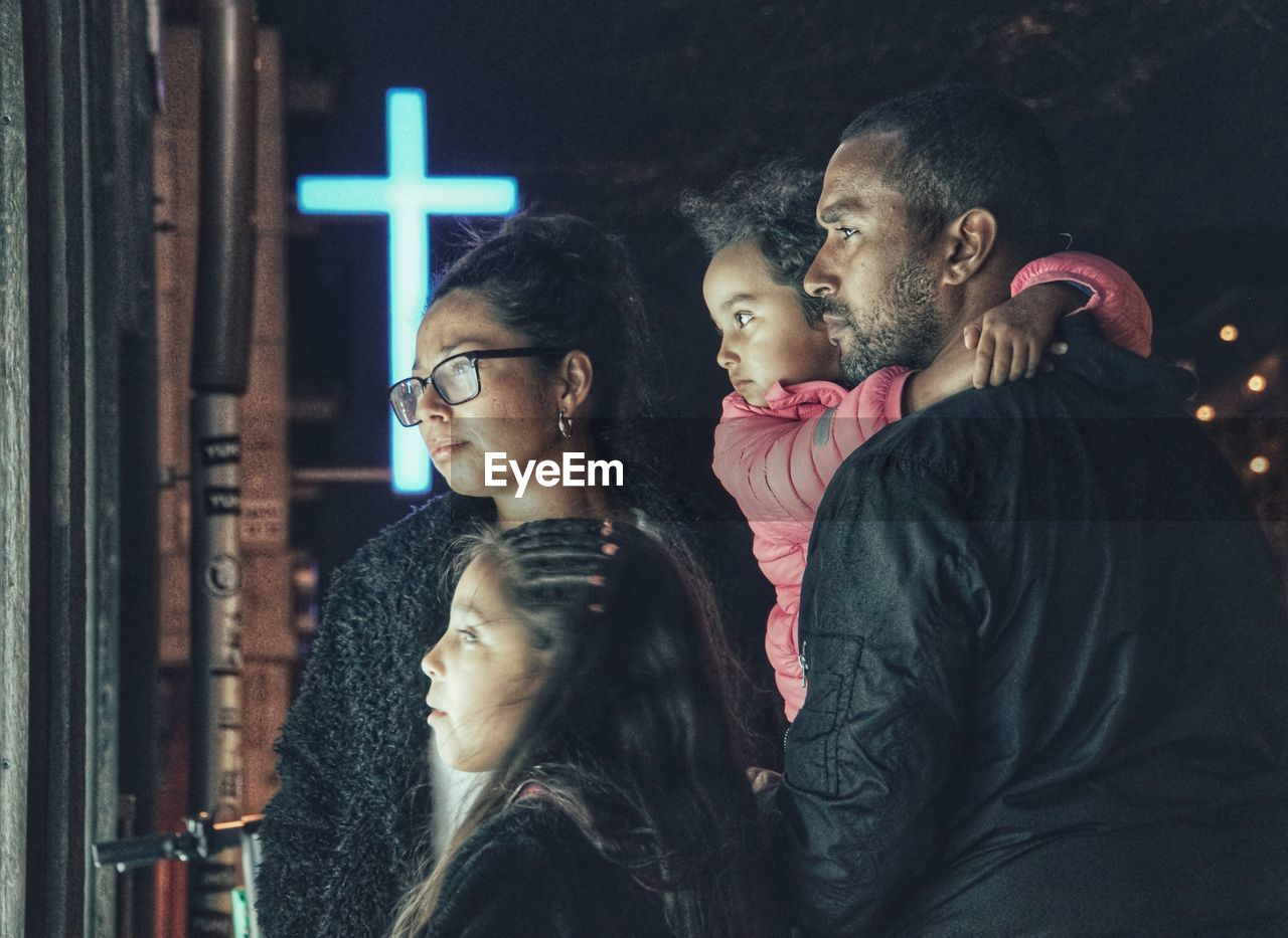 Family looking away while standing in city at night