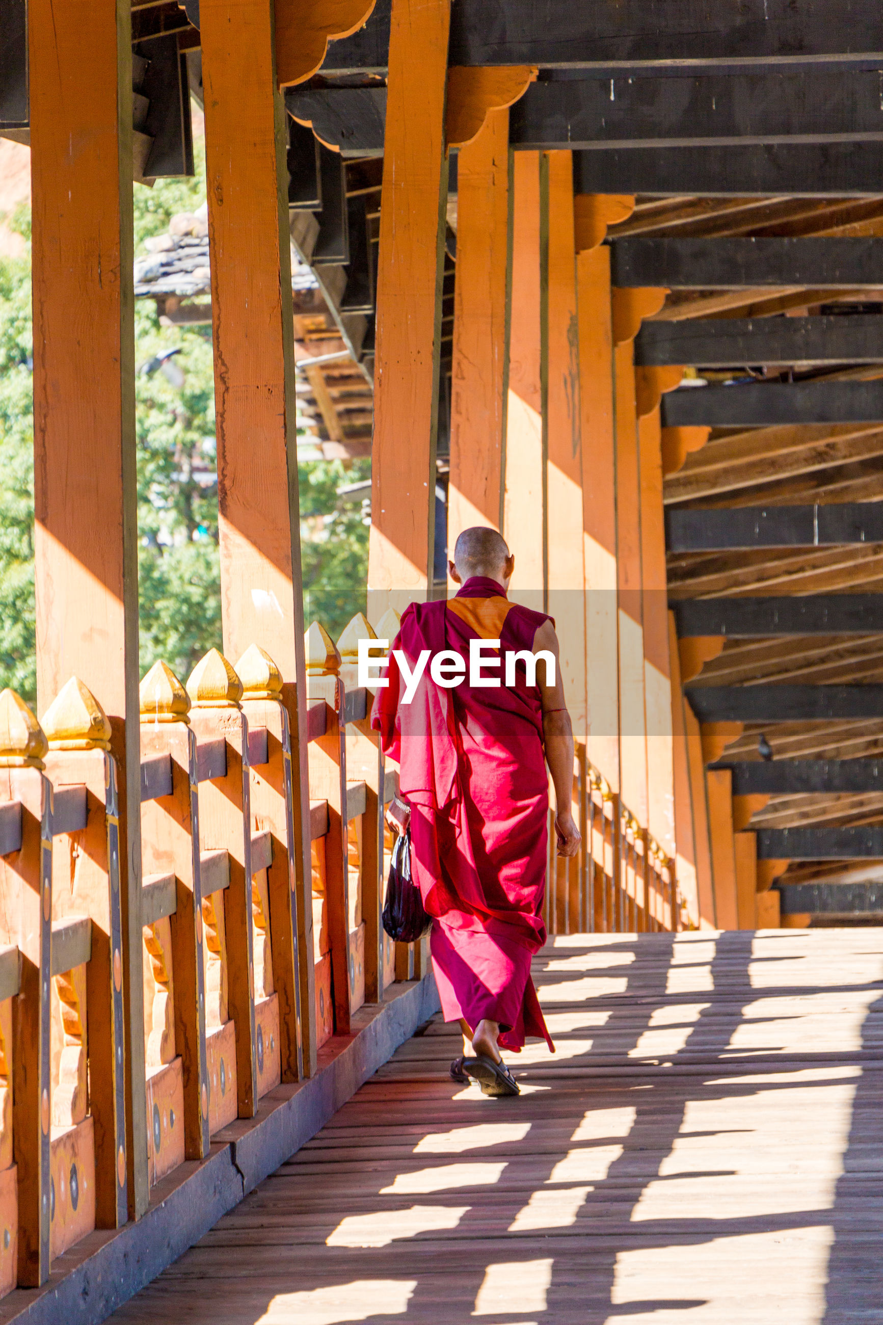 Rear view of monk walking on covered bridge