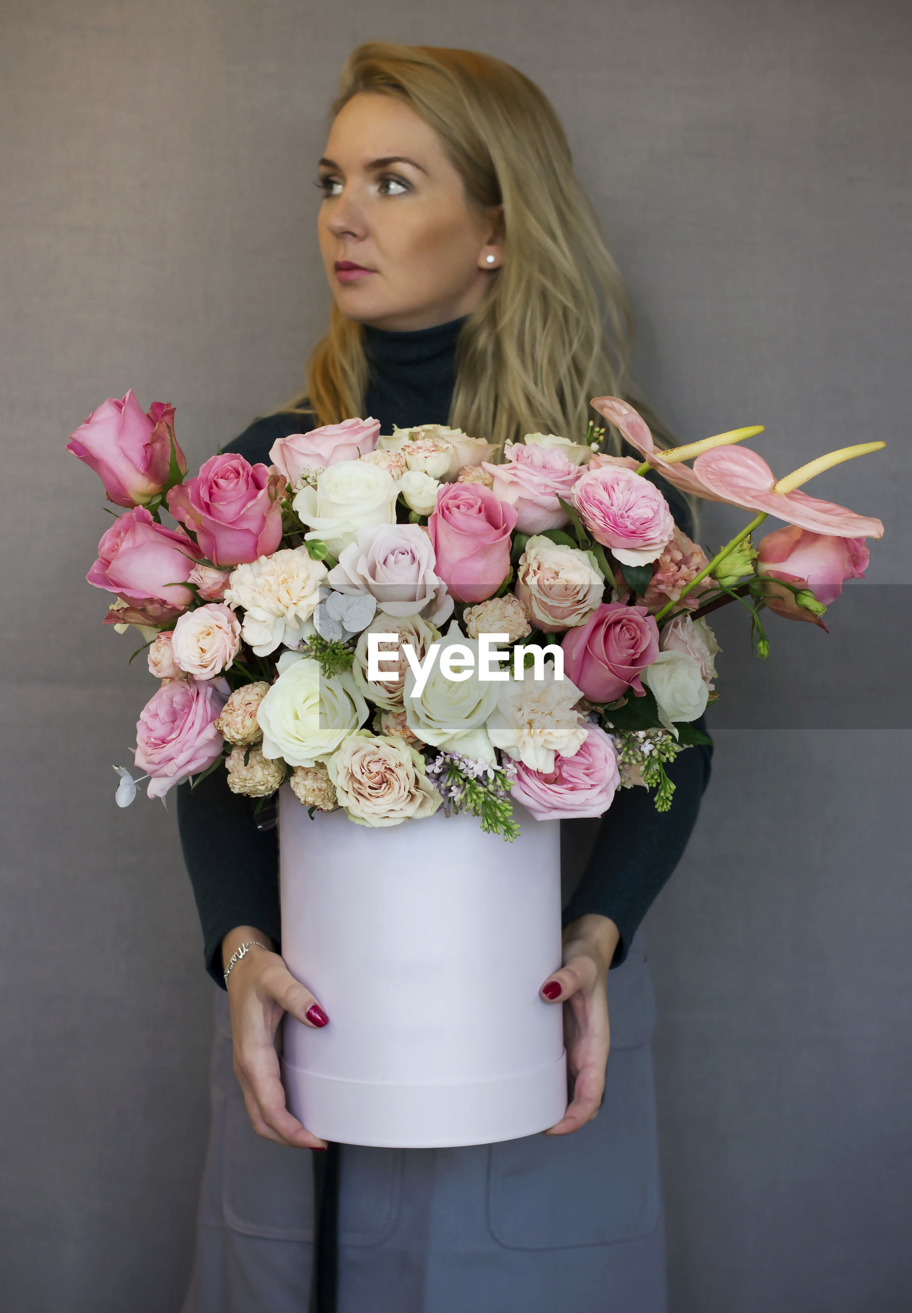 Woman holding flower bouquet while standing against gray wall