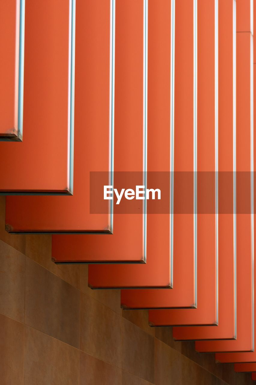 steps and staircases, red, architecture, indoors, built structure, staircase, no people, pattern, railing, day, wall - building feature, absence, building, flooring, orange color, wall, entrance, repetition, empty