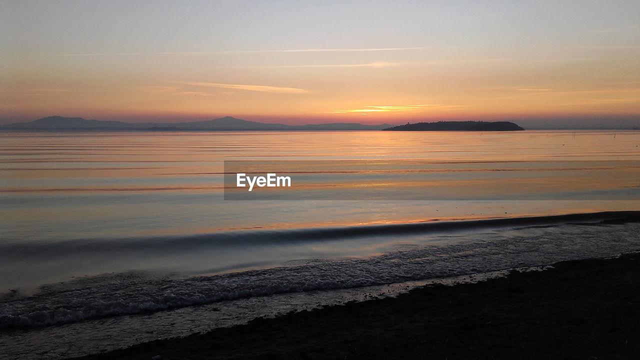 sunset, sky, beauty in nature, scenics - nature, water, sea, tranquility, tranquil scene, beach, cloud - sky, land, orange color, idyllic, horizon over water, horizon, no people, nature, motion, non-urban scene
