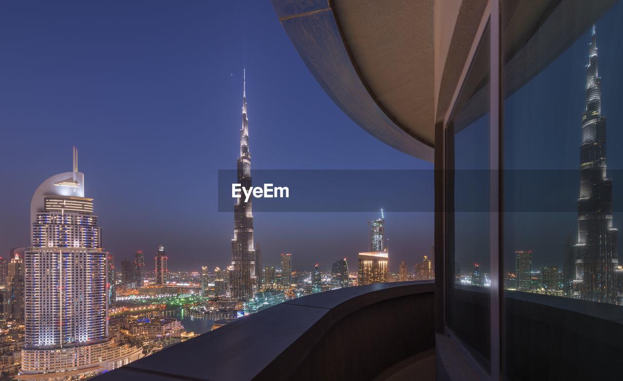 Illuminated City Against Sky Seen From Balcony At Night