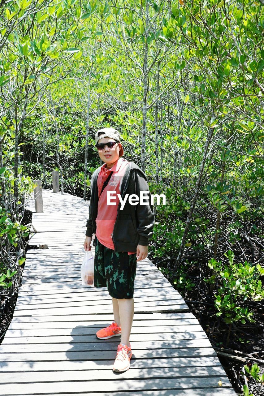 Portrait of mid adult man wearing sunglasses standing on footpath in forest