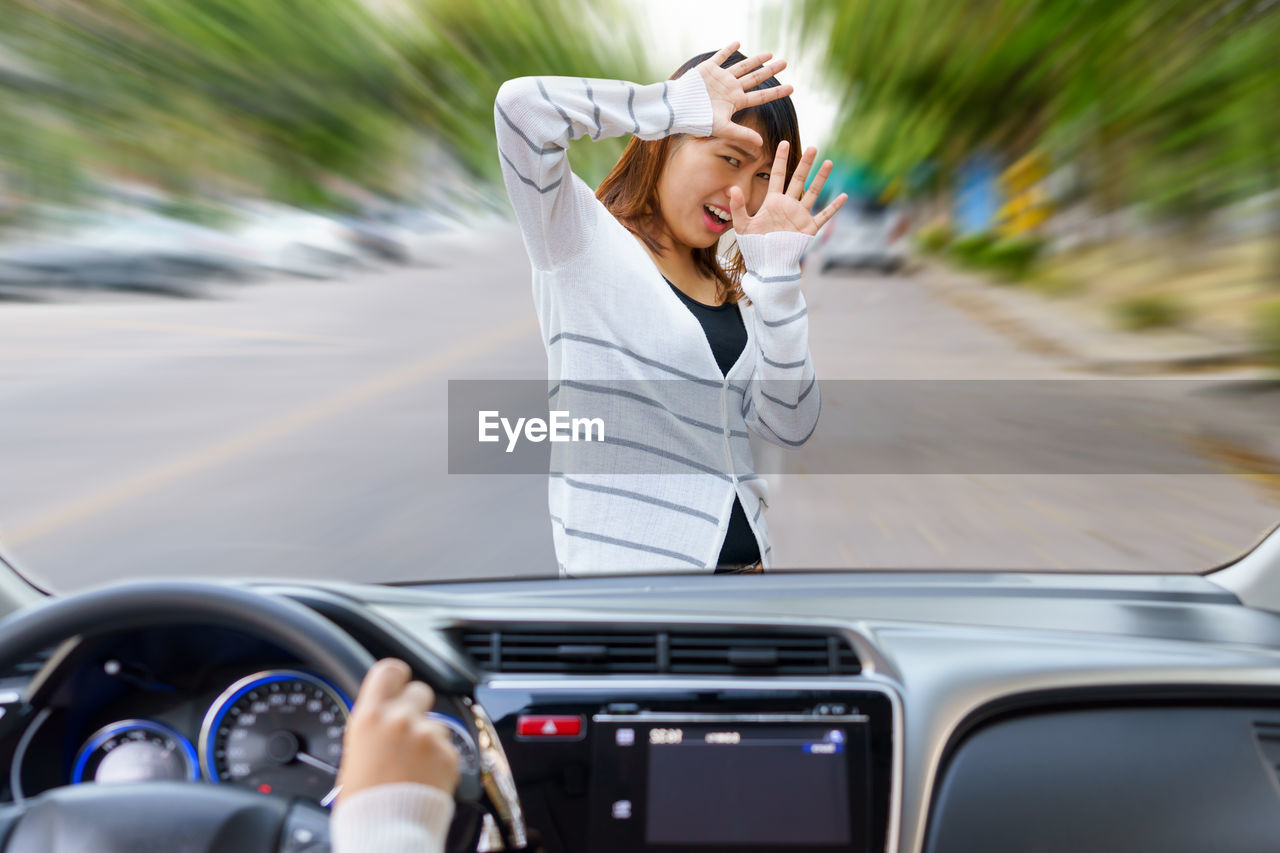 Scared Woman In Front Of Car Seen Through Windshield