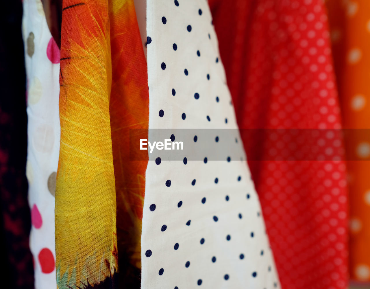 clothing, no people, choice, hanging, pattern, multi colored, indoors, textile, close-up, variation, still life, fashion, polka dot, dress, spotted, white color, in a row, red, day, selective focus, scarf, garment
