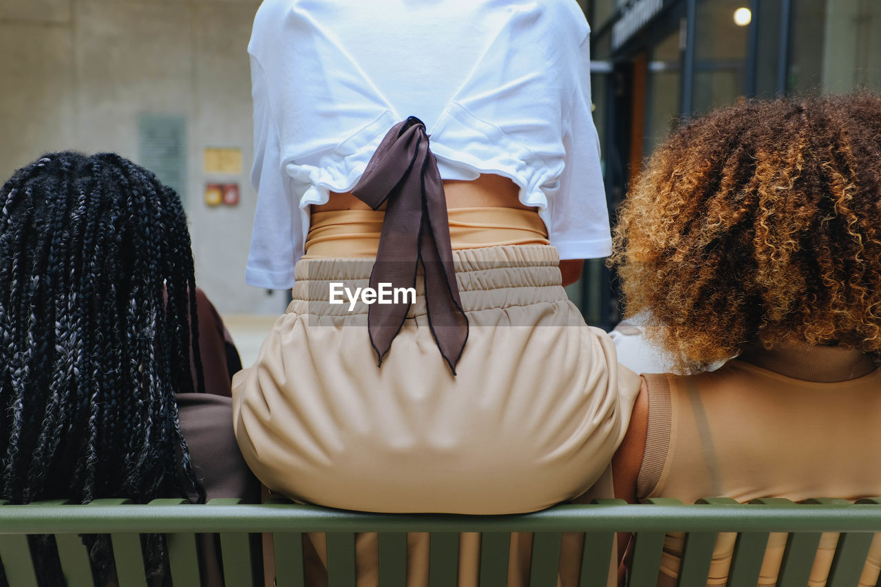 Rear View Of Women Sitting On Bench