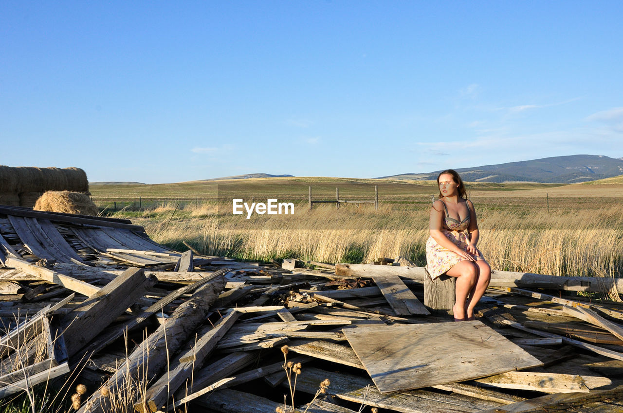 Young Woman Sitting On Log Amidst Broken House On Field Against Sky