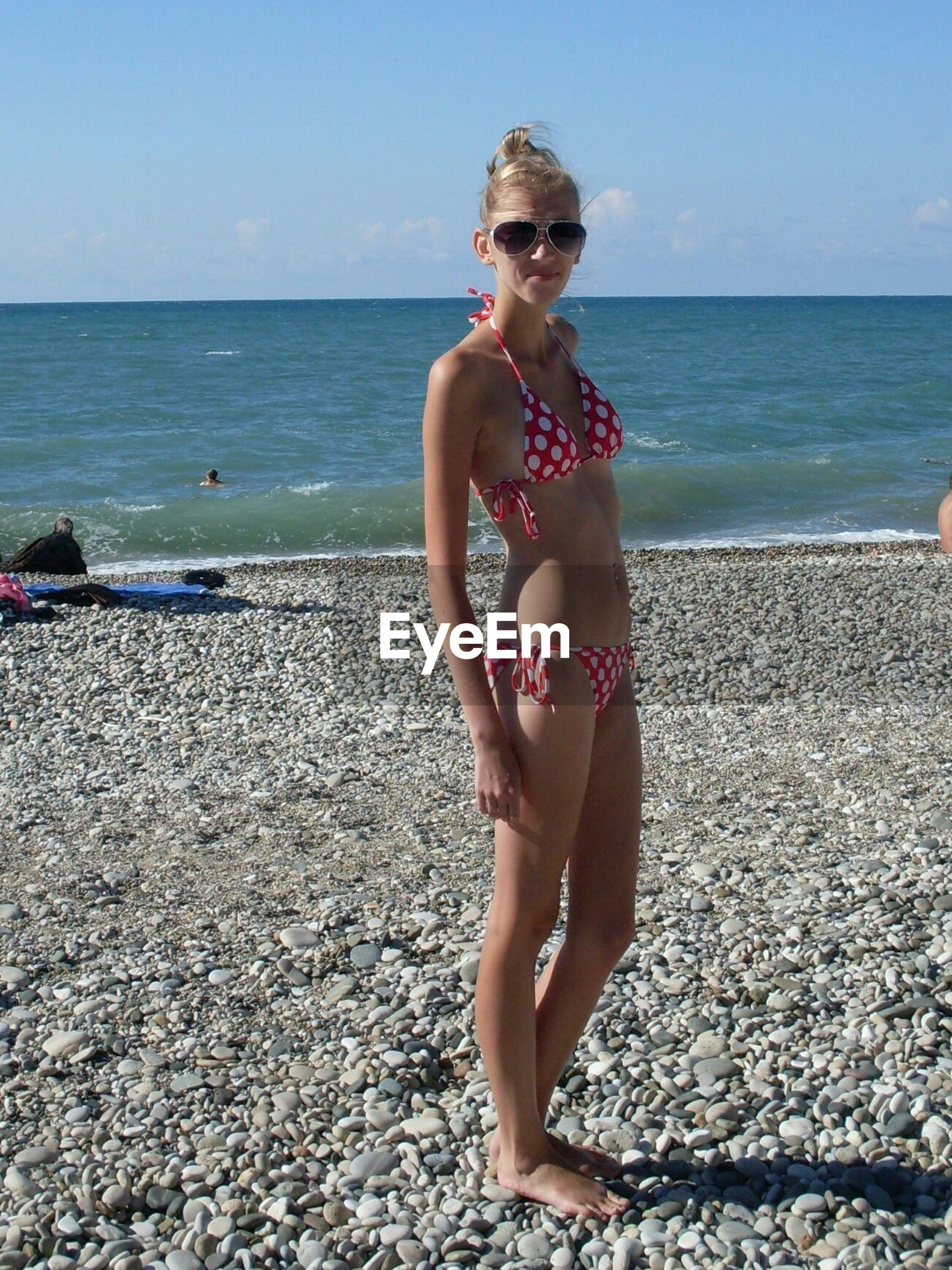 Full length of young woman wearing bikini standing at beach on sunny day