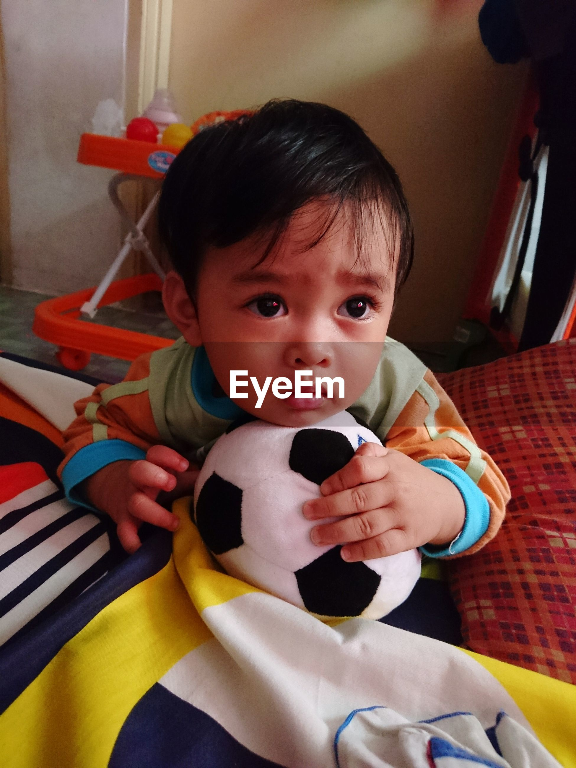 Cute boy with toy looking away while lying on bed at home
