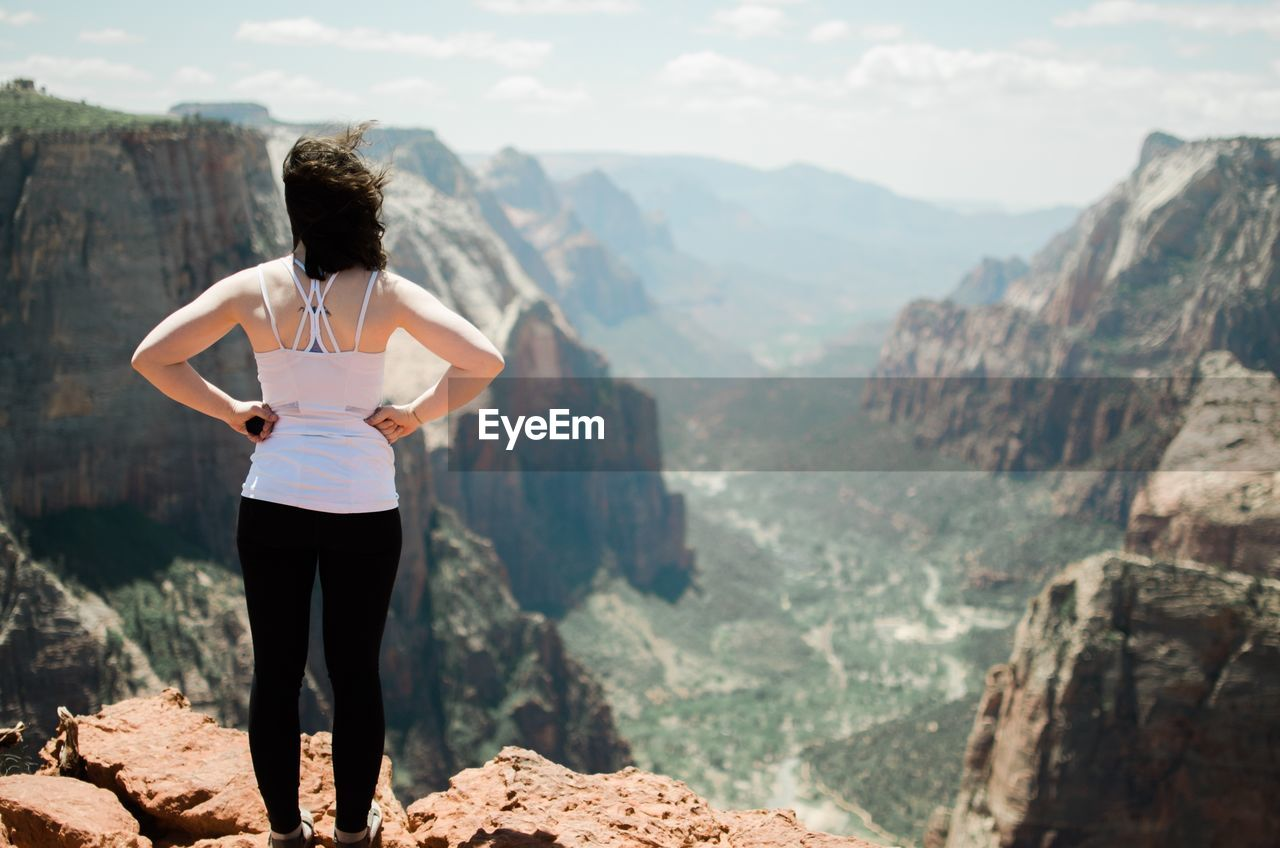 Woman Standing On Rock While Looking At Mountains